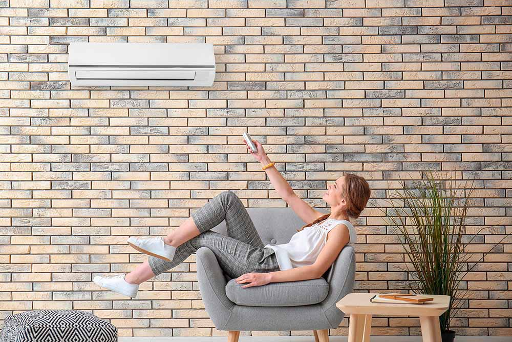 lady on sofa relaxing and turning on air conditioner
