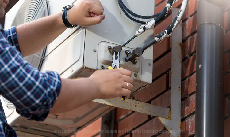 aircond technician fixing the wiring of outdoor unit